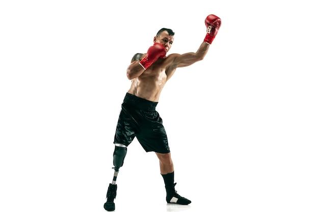 Pełnej długości portret mięśni sportowca z protezą nogi, miejsce. męski bokser w czerwonych rękawiczkach. na białym tle strzał na białej ścianie.