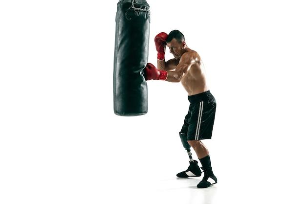 Pełnej długości portret mięśni sportowca z protezą nogi, miejsce. męski bokser w czerwonych rękawiczkach, szkolenia i ćwiczenia. na białym tle na białej ścianie. pojęcie sportu, zdrowego stylu życia.