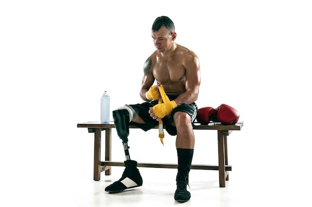 Pełnej długości portret mięśni sportowca z protezą nogi, miejsce. mężczyzna bokser w rękawiczkach przygotowuje się do ćwiczeń. na białym tle na białej ścianie. pojęcie sportu, zdrowego stylu życia.