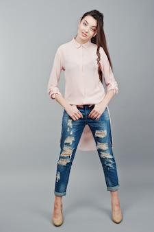 Pełnej długości portret młoda uśmiechnięta brunetka dziewczyna ubrana w różową bluzkę, zgrane dżinsy i kremowe buty
