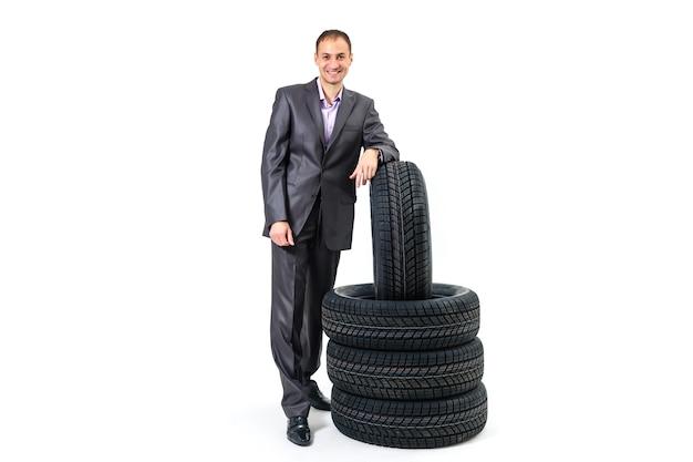 Pełnej długości portret młodego biznesmena opartego na kupie opon samochodowych na białym tle