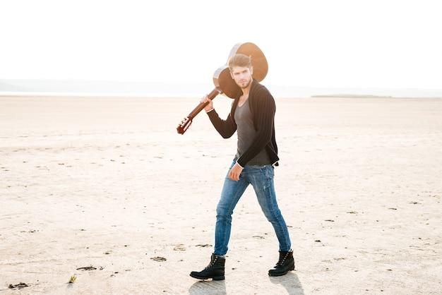 Pełnej długości portret młodego mężczyzny dorywczo spacerującego po plaży i trzymającego gitarę na ramieniu