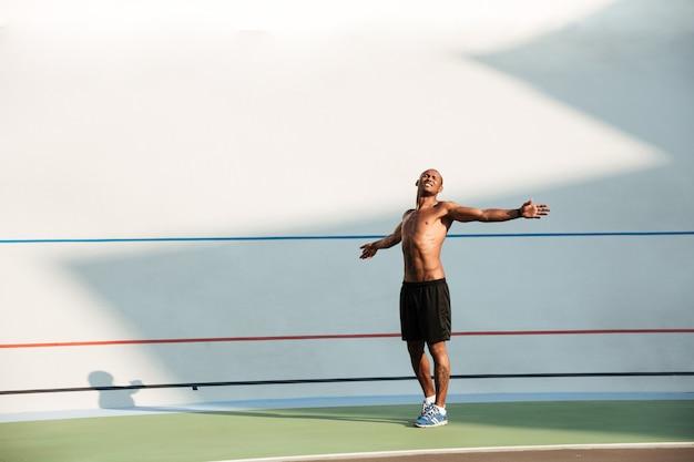 Pełnej długości portret młodego sportowca robi ćwiczenia rozciągające