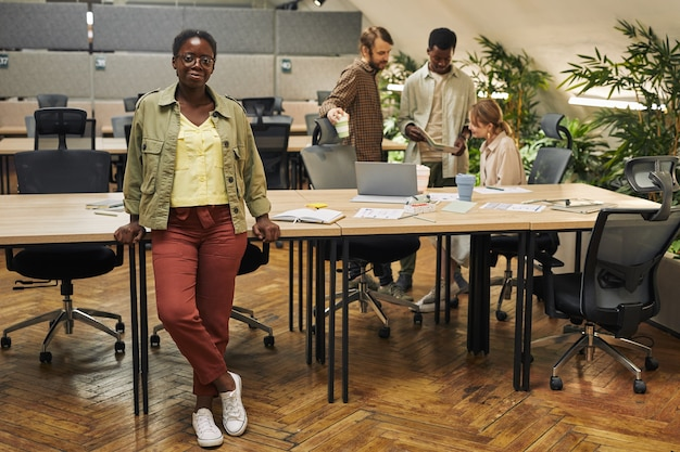 Pełnej długości portret młodej kobiety afroamerykańskiej stojącej opierając się na biurku w nowoczesnym biurze z ludźmi pracującymi na powierzchni, kopia przestrzeń