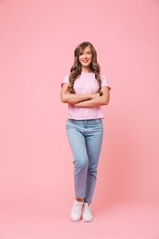 Pełnej długości portret młodej kobiety brunetki lat 20 z długą kręconą fryzurą w swobodnych dżinsach, uśmiechając się do kamery z rękami skrzyżowanymi, odizolowany na różowym tle