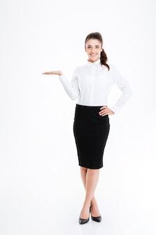 Pełnej długości portret młodej pięknej bizneswoman trzymającej miejsce na kopię na białym tle na białej ścianie