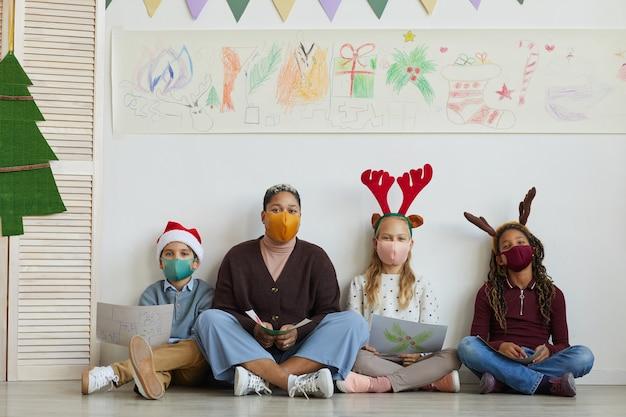 Pełnej długości portret nauczycielki w masce siedzącej na podłodze z wieloetniczną grupą dzieci trzymających zdjęcia podczas zajęć plastycznych w boże narodzenie, skopiuj miejsce