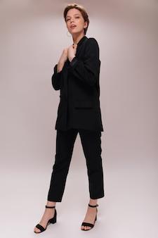 Pełnej długości portret pani w czarnym garniturze. atrakcyjna młoda kobieta w ciemną kurtkę i stylowe spodnie pozuje na na białym tle
