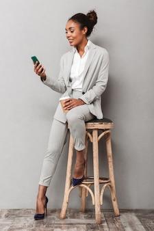 Pełnej długości portret pewnej afrykańskiej kobiety biznesu w garniturze siedzi na krześle, trzymając kawę na wynos, używając telefonu komórkowego