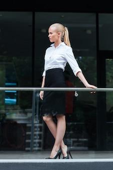 Pełnej długości portret pewnej siebie kobiety stojącej na zewnątrz i opartej na szklanej balustradzie