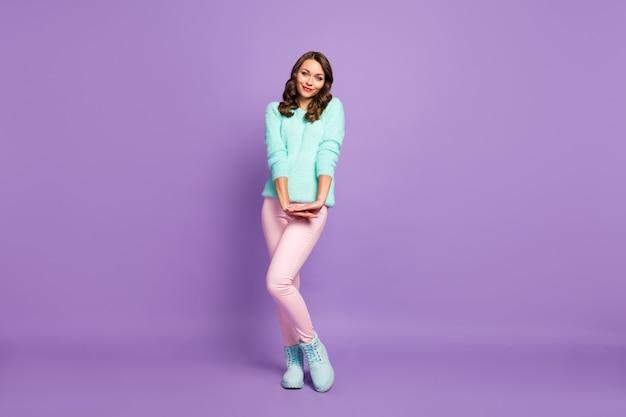 Pełnej długości portret pięknej, falującej kobiety zalotnej w dobrym nastroju kokieteryjnie wyglądającej nieśmiałej osoby nosić turkusowe pastelowe puszyste swetry różowe spodnie niebieskie buty.