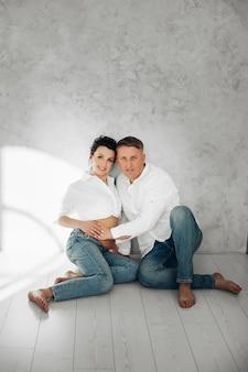 Pełnej długości portret pięknej kobiety w ciąży z mężem dotykając jej brzucha, siedząc na drewnianej podłodze przed szarą teksturą ściany.