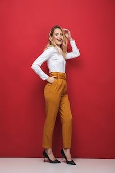 Pełnej długości portret pięknej młodej bizneswoman stojącej na czerwonym tle, pozowanie