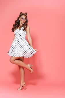 Pełnej długości portret pięknej młodej dziewczyny pin-up na sobie sukienkę i okulary przeciwsłoneczne, stojąc na białym tle, pozowanie
