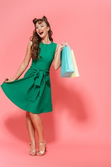 Pełnej długości portret pięknej młodej dziewczyny pin-up na sobie sukienkę stojącą na białym tle, niosąc torby na zakupy
