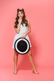 Pełnej długości portret pięknej młodej dziewczyny pin-up na sobie sukienkę stojącą na białym tle, pozowanie, trzymając kapelusz plażowy