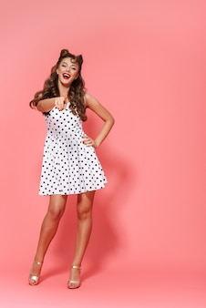 Pełnej długości portret pięknej młodej dziewczyny pin-up na sobie sukienkę stojącą na białym tle, pozowanie