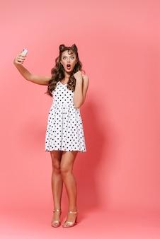 Pełnej długości portret pięknej młodej dziewczyny pin-up na sobie sukienkę stojącą na białym tle, przy użyciu telefonu komórkowego, biorąc selfie