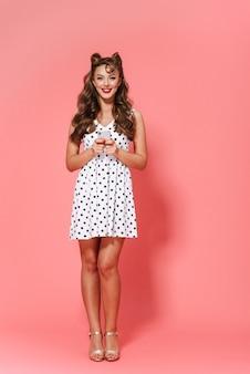 Pełnej długości portret pięknej młodej dziewczyny pin-up na sobie sukienkę stojącą na białym tle, przy użyciu telefonu komórkowego