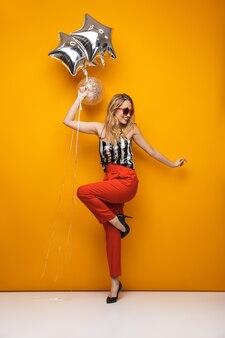 Pełnej długości portret pięknej młodej kobiety blondynka stojącej na żółtym tle, noszących okulary przeciwsłoneczne, pozowanie, trzymając balony