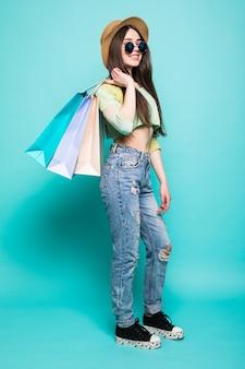 Pełnej długości portret pięknej młodej kobiety z torby na zakupy, na białym tle