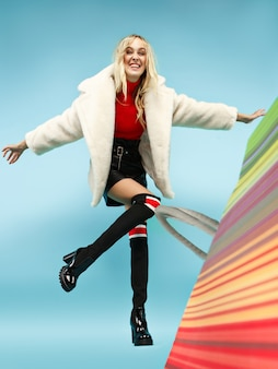 Pełnej długości portret pięknej uśmiechniętej zabawnej blondynki kobiety chodzącej z kolorowych toreb na zakupy na białym tle na niebieskim tle studia.