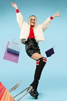 Pełnej długości portret pięknej uśmiechniętej zabawnej blondynki kobiety idącej z kolorowymi torbami na zakupy