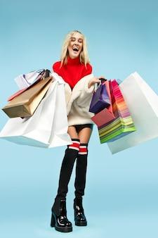 Pełnej długości portret pięknej uśmiechniętej zabawnej blondynki kobiety spaceru z kolorowymi torbami na zakupy na białym tle na niebieskim tle studia. styl życia, moda, sprzedaż, koncepcja zakupoholików