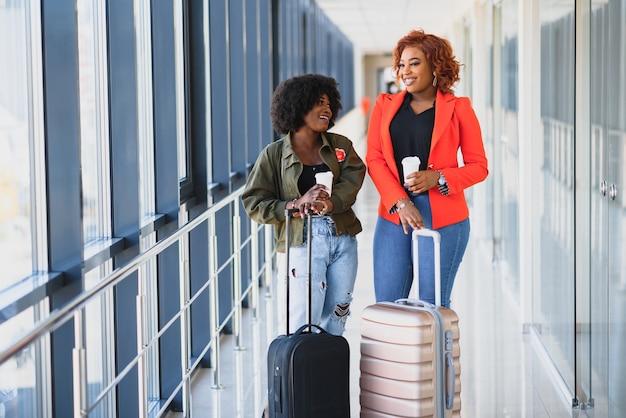 Pełnej długości portret po stronie młodej czarnej kobiety spaceru z walizką na lotnisku