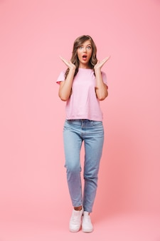 Pełnej długości portret podekscytowanej brunetki kobiety z długimi kręconymi włosami w podstawowej odzieży podnoszącej ręce z zaskoczenia i pozującej z otwartymi ustami, odizolowanej na różowym tle