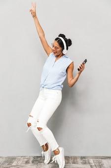 Pełnej długości portret podekscytowanej młodej kobiety w okularach przeciwsłonecznych na białym tle, trzymając telefon komórkowy, słuchanie muzyki w słuchawkach, taniec