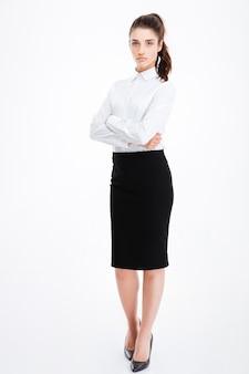Pełnej długości portret poważnej bizneswoman stojącej z założonymi rękoma na białym tle na białej ścianie