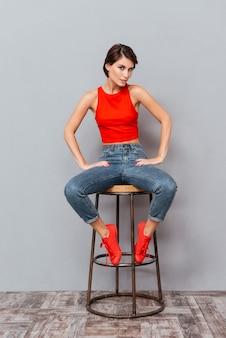 Pełnej długości portret poważnej dziewczyny brunetka siedzi na krześle na białym tle na szarym tle