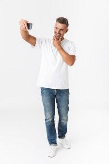 Pełnej długości portret pozytywnego mężczyzny 30s ubranych dorywczo t-shirt i dżinsy biorąc selfie zdjęcie na telefonie komórkowym, trzymając w ręku na białym tle