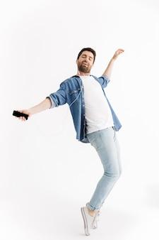 Pełnej długości portret przystojnego brodatego mężczyzny noszącego zwykłe ubrania, skaczącego na białym tle, słuchającego muzyki przez słuchawki, trzymającego telefon komórkowy, tańczącego