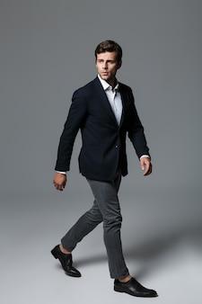 Pełnej długości portret przystojny młody biznesmen ubrany w garnitur na białym tle nad szarą ścianą, pozowanie, odwracając wzrok, chodzenie