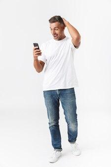 Pełnej długości portret radosnego mężczyzny w wieku 30 lat w swobodnym t-shirt i dżinsach przy użyciu telefonu komórkowego, trzymając w ręku na białym tle