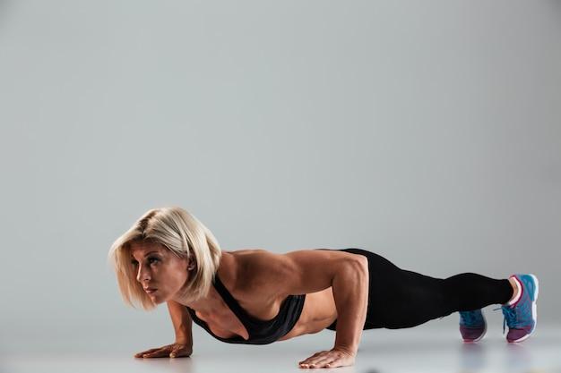 Pełnej długości portret silnej mięśniowej dorosłej sportsmenki