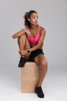 Pełnej długości portret silnej młodej afrykańskiej sportsmenki na białym tle na szarym tle, odpoczywając siedząc i słuchając muzyki przez słuchawki