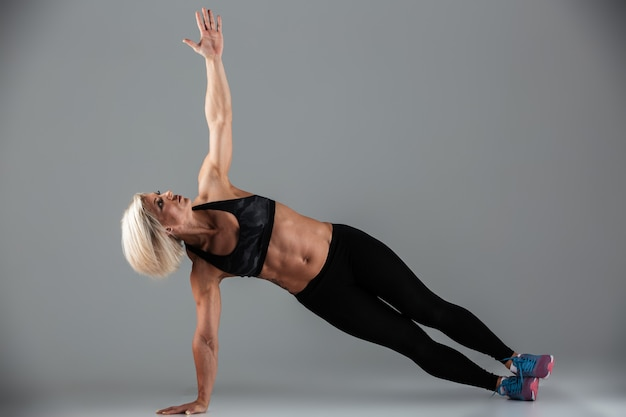 Pełnej długości portret silnej muskularnej kobiety dorosłej