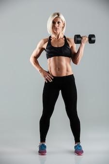 Pełnej długości portret skoncentrowanej mięśniowej sportsmenki