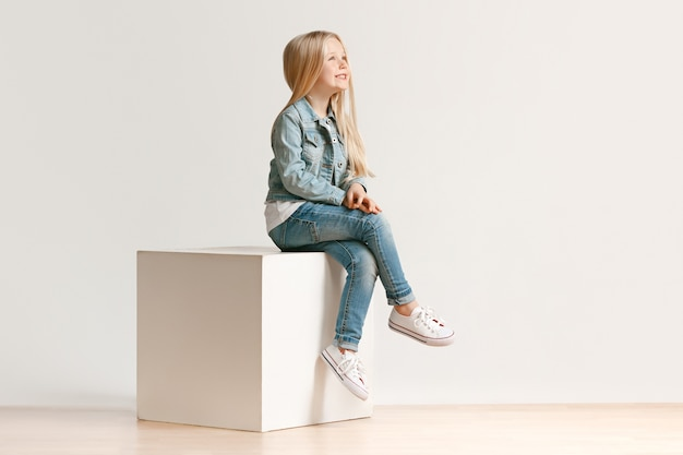 Pełnej długości portret słodkie małe dziecko dziewczynka w stylowe dżinsy ubrania i uśmiechnięty, stojący na białym tle. koncepcja mody dla dzieci