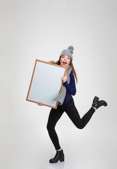 Pełnej długości portret śmiesznej kobiety trzymającej pustą deskę na białym tle na białej ścianie