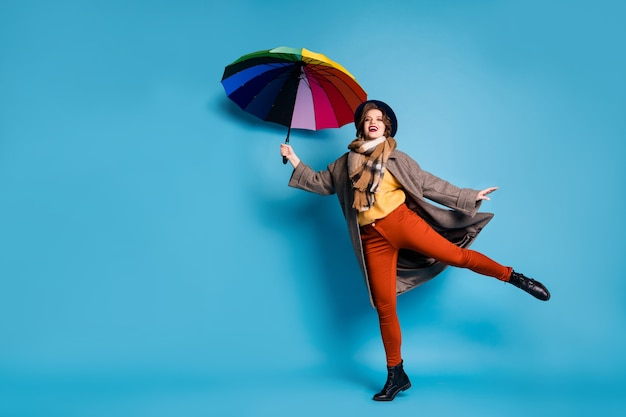Pełnej długości portret śmiesznej podróżniczki podnoszącej się trzymaj kolorowy parasol dmuchany nosić na co dzień długi szary płaszcz sweter pomarańczowe spodnie kapelusz obuwie.