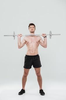Pełnej długości portret sprawnego sportowca podnoszącego ciężką sztangę