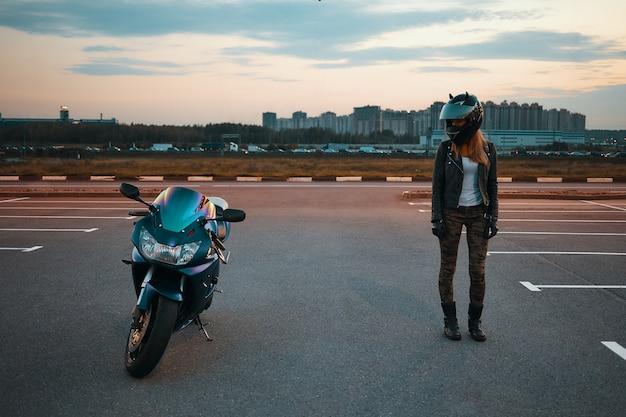 Pełnej długości portret stylowej młodej kobiety rasy kaukaskiej w dżinsach khaki, czarnej skórzanej kurtce i kasku ochronnym stojącej na parkingu i patrząc na niebieski motocykl zaparkowany obok niej