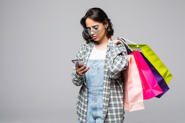 Pełnej długości portret szczęśliwa młoda kobieta trzyma torby na zakupy i telefon komórkowy na białym tle