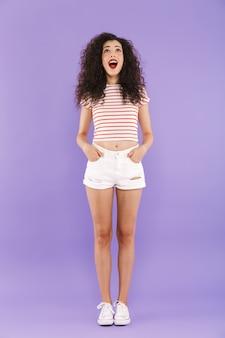 Pełnej długości portret szczęśliwa młoda kobieta z kręconymi włosami w letnim streetwear, uśmiechając się i patrząc w górę