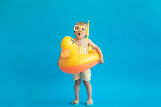 Pełnej długości portret szczęśliwego dziecka z żółtą gumową kaczką przeciw niebieskiej ścianie.