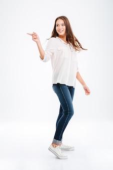Pełnej długości portret szczęśliwej dorywczo kobiety wskazującej palcem na białym tle na białej ścianie